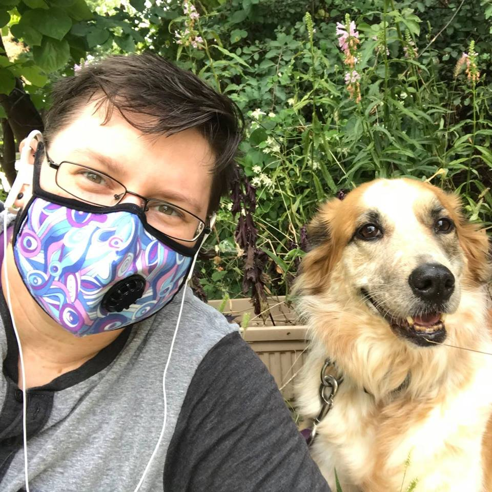 Image description: A photo of Skylar Ashton Kantola, a white neuroqueer disabled trans person, and one of their pups, Cricket, a orange and creme shepard mutt, laying down together on steps with tall plants behind them both. Skye is wearing a gray and black-accented henley shirt, rectangular eye classes, white headphones, and a trans and genderfluid pride-colored breathing mask. Skye and Cricket look relaxed and happy together and are enjoying the lovely summer weather!