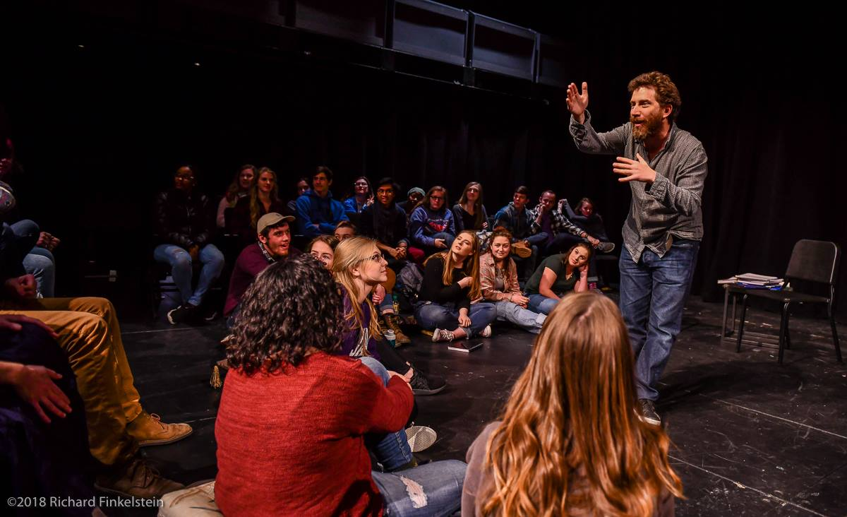 Image description: A photo Julian Boal on a stage with a microphone as he facilitates a theatre of the oppressed session in 2018.  Many participants are visible surrounding him in a theatre-style seating surrounding the stage.