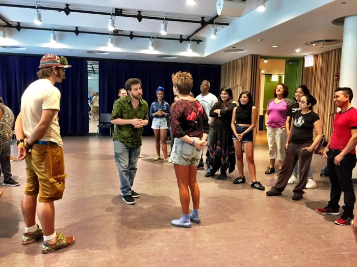 Photo of a TO workshop in which Julian Boal is jokering. Julian and a workshop participant stand in the center of a loose circle of other participants. Julian and the participant make eye contact facing each other as the other participants look on with humor.