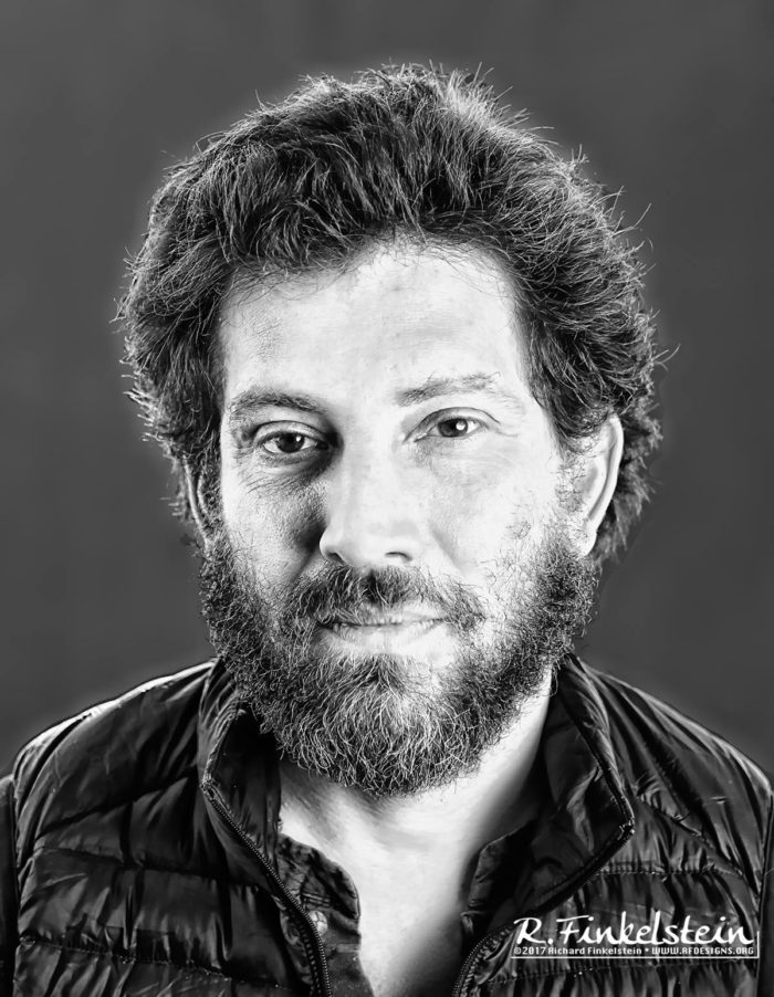 A professional headshot photo of Julian Boal. Julian is smiling and facing the camera and the photo is in grayscale.
