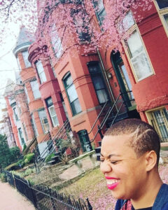 A photo of Je standing on a street lined with brick apartments. Je is lauching and only her head is visible. She has cool designs shaved into her hair.