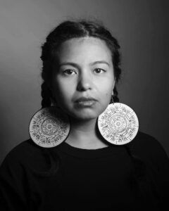 A black and white photo of Tania from the shoulders up. She has her hair braided on either side, is wearing large circular earrings which have indigenous art on them, and she is facing the camera.
